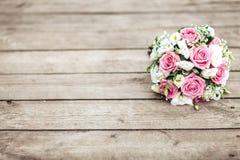 En brud- bukett av en brud från vita och rosa rosor ligger på en träbakgrund, horisontellt Royaltyfria Foton