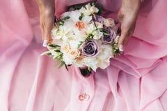 En brud- bukett av kräm- pioner och purpurfärgade rosor som bruden tar i händer Arkivfoto