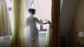 En brud, härlig flicka, skyler in, och vit peignoir, ämbetsdräkt, ser ut fönstret Morgon av bruden lager videofilmer