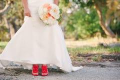 En brud i röda skor. Royaltyfri Foto