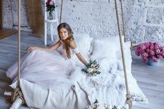 En brud med frisyren och smink i ursnygg rosa bröllopsklänning och en vail med en bukett av pioner Royaltyfri Fotografi