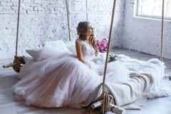 En brud med frisyren och smink i ursnygg rosa bröllopsklänning och en vail med en bukett av pioner Royaltyfria Foton