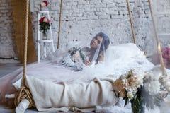 En brud med frisyren och smink i ursnygg rosa bröllopsklänning och en vail med en bukett av pioner Arkivbild