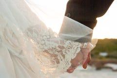 En brud och en brudgum med händer för tappningbröllopsklänninghåll som går på en strand in mot solnedgången arkivbilder