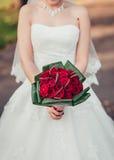 En brud som rymmer hennes röda bröllopbukett av blommor Royaltyfri Foto