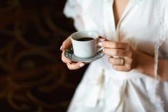 En bruds morgon, kaffe för frukost, genomskinlig vit peignoir och försiktiga händer En bild av en elegant kvinnlig hand med royaltyfri fotografi