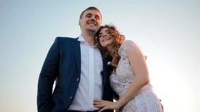 En bruid en bruidegom die lachen omhelzen stock videobeelden