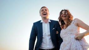 En bruid en bruidegom die lachen omhelzen stock footage