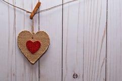 En brun hjärta på en linje framme av ett staket Royaltyfri Bild