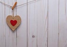 En brun hjärta på en linje framme av ett staket Royaltyfri Fotografi