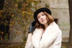 En brunettdam i hatt och handskar och laget står räta ut hennes hatt med hennes hand retro utomhus Arkivfoto