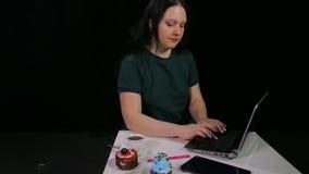 En brunettflicka i ett kaf? arbetar med en dator och dricker kaffe i ett kaf? arkivfilmer