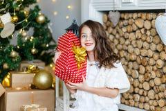 En brunettgilr framme av päls-trädet och spisen med stearinljus och gåvor Drömma för flicka Helgdagsafton för ` s för nytt år Jul fotografering för bildbyråer