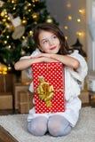 En brunettgilr framme av päls-trädet och spisen med stearinljus och gåvor Drömma för flicka Helgdagsafton för ` s för nytt år Jul arkivfoto