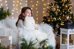 En brunettgilr framme av päls-trädet och spisen med stearinljus och gåvor Drömma för flicka Helgdagsafton för ` s för nytt år Jul royaltyfri fotografi
