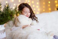 En brunettgilr framme av päls-trädet och spisen med stearinljus och gåvor Drömma för flicka Helgdagsafton för ` s för nytt år Jul arkivbild
