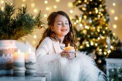 En brunettgilr framme av päls-trädet och spisen med stearinljus och gåvor En flicka som gör en önska julhelgdagsaftongåvor semest arkivbild