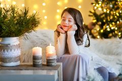 En brunettgilr framme av päls-trädet och spisen med stearinljus och gåvor En flicka som gör en önska julhelgdagsaftongåvor semest royaltyfri bild