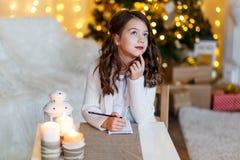 En brunettgilr framme av päls-trädet som skrivar ett brev till Santa Claus Drömma för flicka Helgdagsafton för ` s för nytt år Ju arkivbild