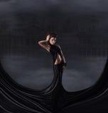 En brunettkvinna i en svart klänning på en mörk bakgrund Arkivfoton