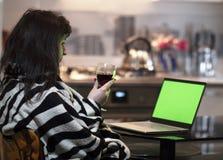 En brunettkvinna sitter med ett exponeringsglas av vin i hemaftonen och ser en bärbar datorskärm, chromakey royaltyfri foto