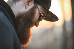 En brutal ung man med ett enormt skägg i solglasögon och ett lock i träna på solnedgången royaltyfri foto