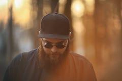 En brutal ung man med ett enormt skägg i solglasögon och ett lock i träna på solnedgången royaltyfri fotografi
