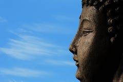En buddha mot en blå himmel för insikt fotografering för bildbyråer