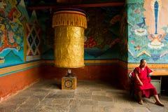 En buddistisk munk sitter med en stor bön rullar in den Punakha fästningkloster, Paro, Bhutan Royaltyfri Bild