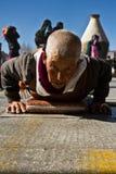 En buddistisk nunna och hennes prosotrations, Jokhang tempel Lhasa Tibet Royaltyfria Bilder