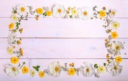 En bukett av cosmeaen eller kosmos för vita blommor med bandet på vita bräden Trädgårds- guling blommar över handgjort trä Royaltyfria Foton