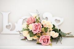 En bukett av delikata blommor med en inskriftFÖRÄLSKELSE royaltyfria bilder