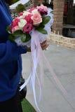 En bukett av en brud från vita och rosa rosor i händerna av en kvinna Royaltyfri Bild