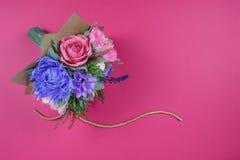 En bukett av färgrika pappers- blommor på en magentafärgad bakgrund som en bakgrund för en vykort, en inbjudanbokstav och ett etc arkivbilder