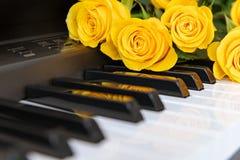En bukett av gula rosor p? pianot Musikaliskt begrepp Bakgrund kopiera avst?nd royaltyfri foto