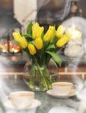 En bukett av gula tulpan i en vas i inre av ett retro Royaltyfria Bilder