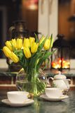 En bukett av gula tulpan i en vas i inre av ett retro Arkivbilder