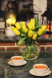 En bukett av gula tulpan i en vas i inre av ett retro Royaltyfria Foton