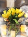 En bukett av gula tulpan i en vas i inre av ett retro Arkivfoto