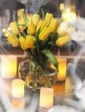 En bukett av gula tulpan i en vas i inre av ett retro Arkivfoton