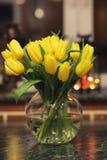 En bukett av gula tulpan i en vas i inre av ett retro Fotografering för Bildbyråer
