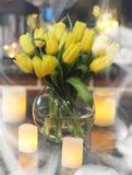 En bukett av gula tulpan i en vas i inre av ett retro Royaltyfri Foto