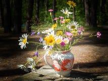 En bukett av lösa blommor i en vas Arkivfoto