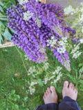 En bukett av lösa blommor och ett kvinnafotanseende på gräset royaltyfri fotografi