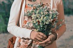 En bukett av lösa lösa blommor av tusenskönor i händerna av en iklädd flicka en blommatryckklänning och en påse på hennes höger a royaltyfria bilder
