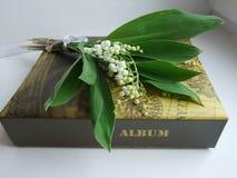 En bukett av liljekonvaljer och albumet Royaltyfria Foton