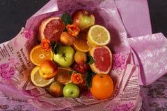 En bukett av nya frukter med citruns och rosor som slås in i färgrikt inpackningspapper Fruktbukett med nya frukter och blommor Royaltyfri Foto