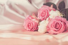 En bukett av nya rosor på en bakgrund av siden- tyg kopiera avstånd Celebratory begrepp toning royaltyfri foto