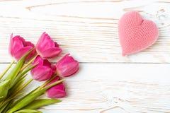 En bukett av nya tulpan och en rosa färg stack hjärta på en vit träbakgrund Arkivfoto