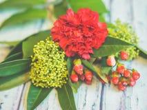 En bukett av röda och gröna blommor som ligger på en trätabell mot mjuk-fokuserad bakgrund Arkivbild